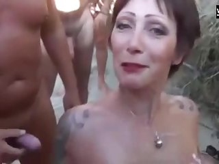 A beautiful French Beach slut sucks one dick after the successive and gets showered with cum.